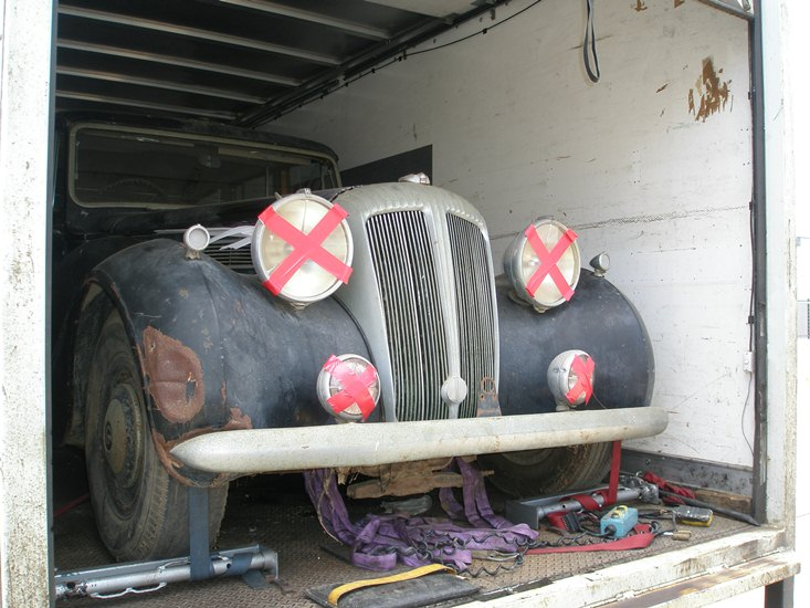 Daimler, loaded on truck, with headlights taped to prevent damage to the galss