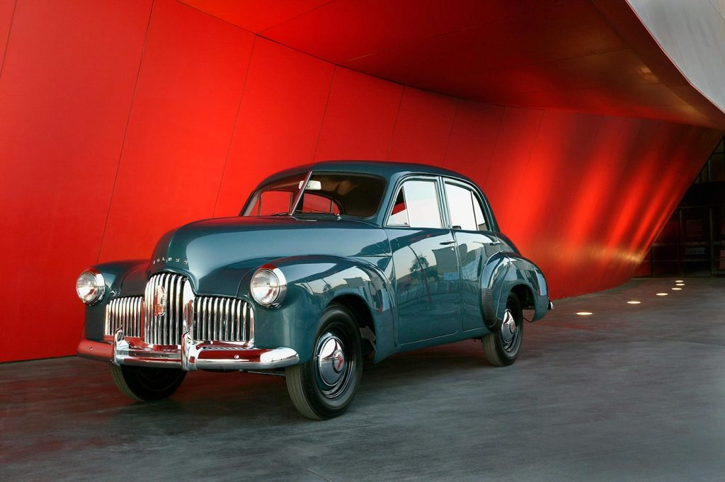 Four door, blue-gunmetal grey sedan with chrome-plated radiator grille, bumper bars, and hub caps. The red entryway to the Museum forms a backdrop.